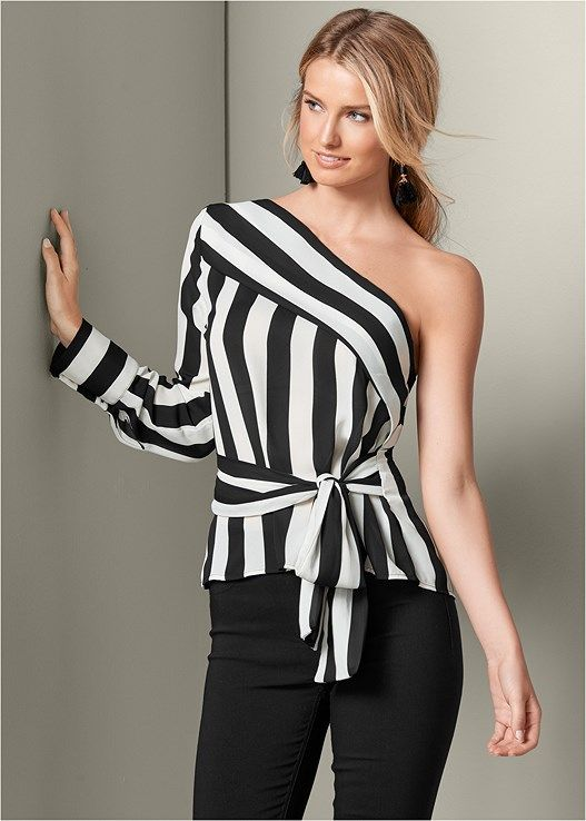 The stripes and angles of this bold one shoulder top help to make it unforgettable! Softened by the loose fit and draping of the generous tie at the waist, this top pairs well with both wide-leg pants, leggings, or fitted capris. Take advantage of all that exposed skin to add shiny statement jewelry and leave your stylish mark wherever you wear this top! Stripe placement may varyOne shoulder styleFunctional buttons at cuffFunctional tie at waistPoly. Imported